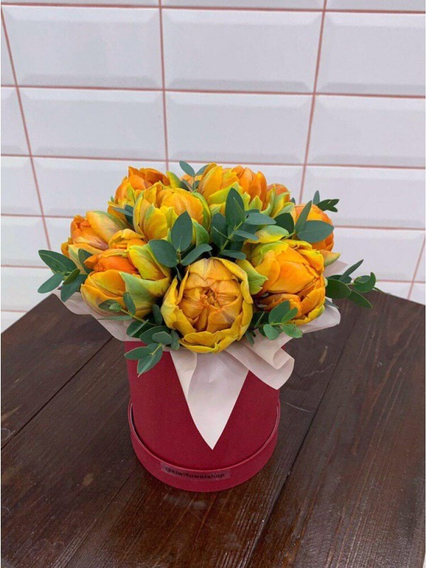 Composition of yellow tulips in a hat box 'Orange sunset' by Kiwi Flower Shop