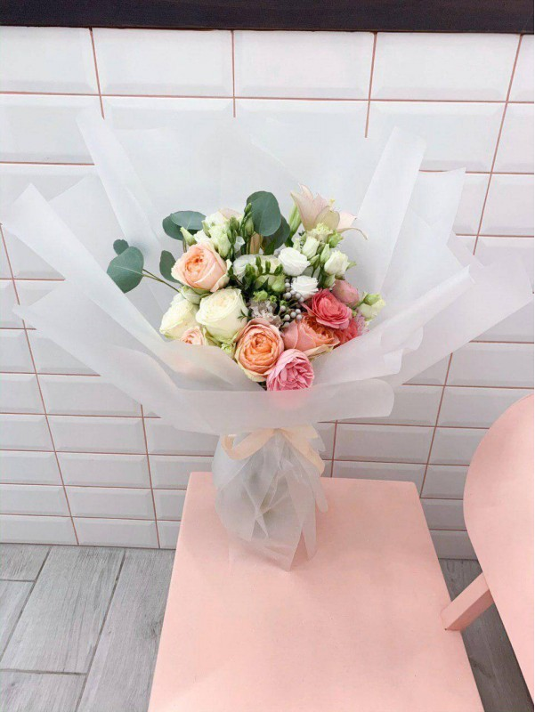 Combined bouquet in transparent tracing paper 'Pastel flower mix' by Kiwi Flower Shop